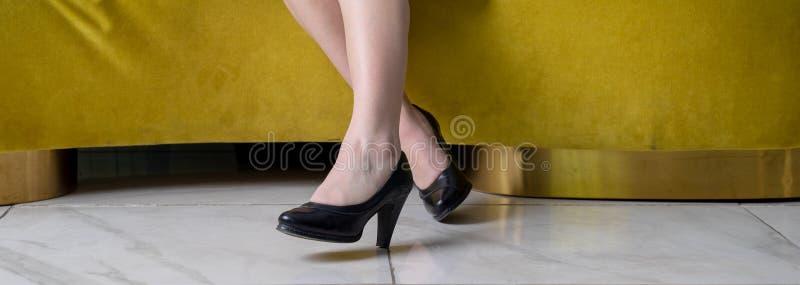 Nahaufnahme von schönen weiblichen Beinen in den schwarzen Stöckelschuhen auf gelbem Sofa, Fahne stockbilder