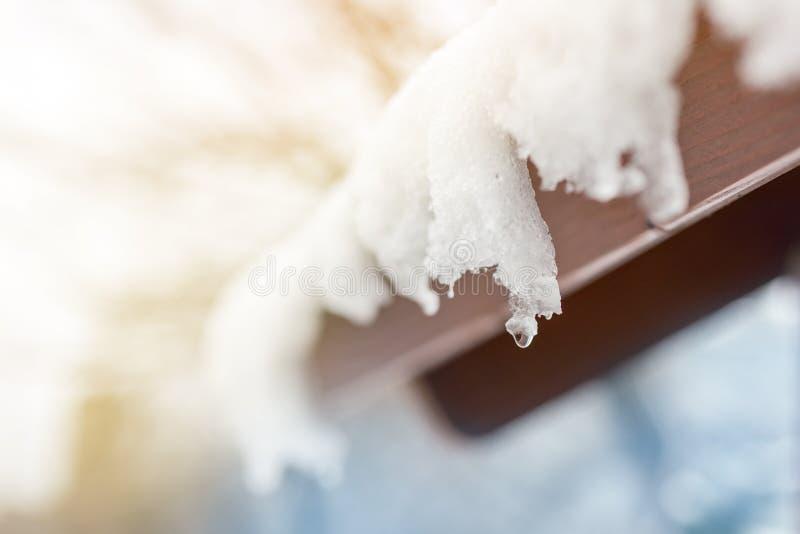 Nahaufnahme von schmelzenden Schneeeiszapfen auf Dach Fallende Wassertropfen Anfang des Frühlinges Treffen des Kälte- und Hitzeko stockfotos