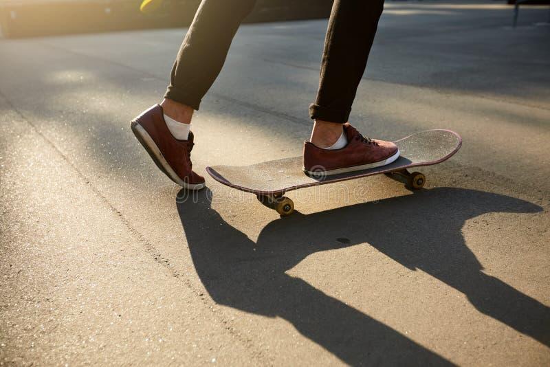 Nahaufnahme von Skateboardfahrerfüßen beim Eislauf in Rochenpark Mannreiten auf Skateboard Lokalisierte Ansicht, Froschperspektiv lizenzfreies stockbild