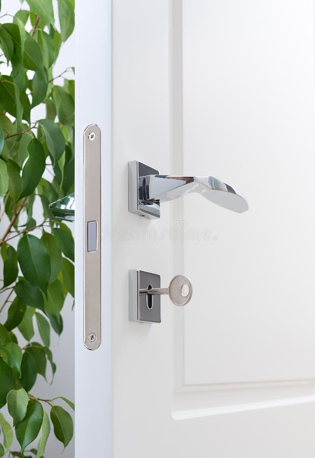Nahaufnahme von Türinstallationen Eine weiße Tür mit modernen Chromgriffen, Türschloss mit Schlüssel stockfotos