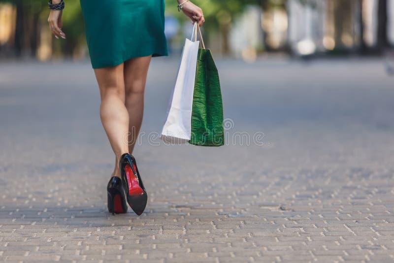 Nahaufnahme von tragenden Einkaufstaschen der jungen Frau beim Gehen entlang die Stra?e Reizvolle Fahrwerkbeine der Frau mit Hand lizenzfreie stockbilder