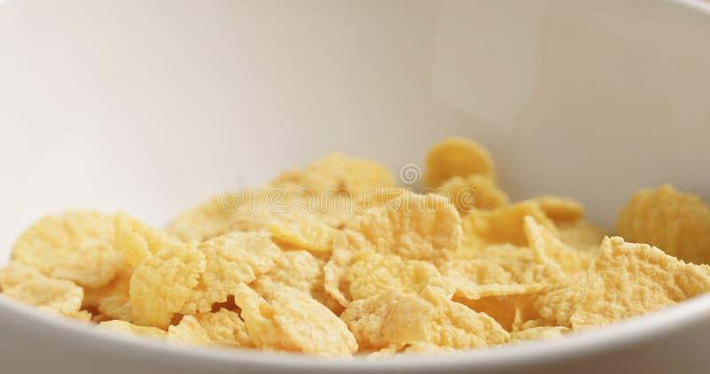 Nahaufnahme von trockenen Corn Flakes in der weißen Schüssel auf hölzerner Tabelle stockbilder