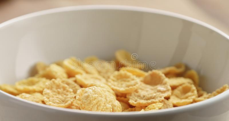 Nahaufnahme von trockenen Corn Flakes zum Frühstück in der Schüssel auf Tabelle stockfotos