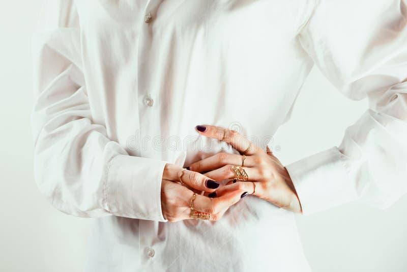 Nahaufnahme von weiße Frau ` s Händen mit verschiedenen Ringen um ihre Taille, weißes Hemd, weißer Hintergrund lizenzfreie stockbilder