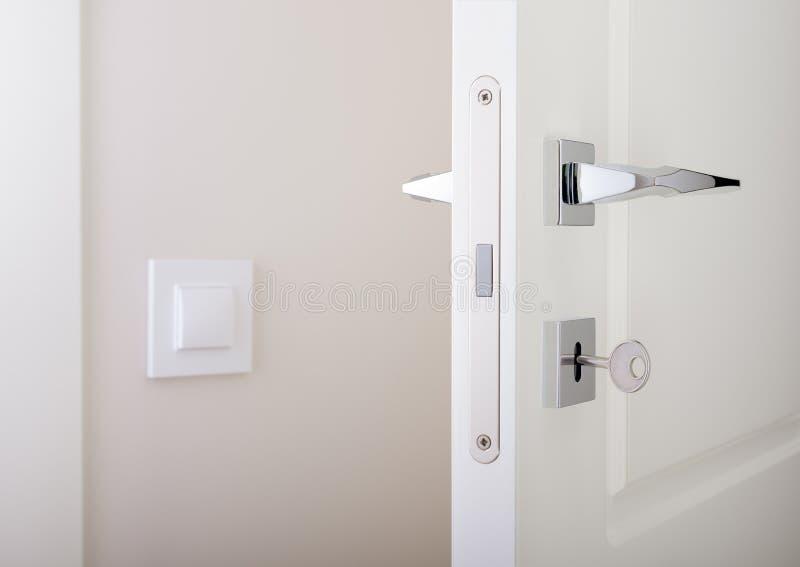 Nahaufnahme von weißen Innentüren Schließen Sie mit Schlüssel und Chromtürgriff zu lizenzfreies stockbild