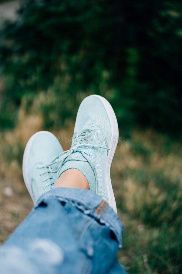 Nahaufnahme von weiblichen Beinen in den Jeans und in den Turnschuhen auf einem Hintergrund von Bäumen stockbild