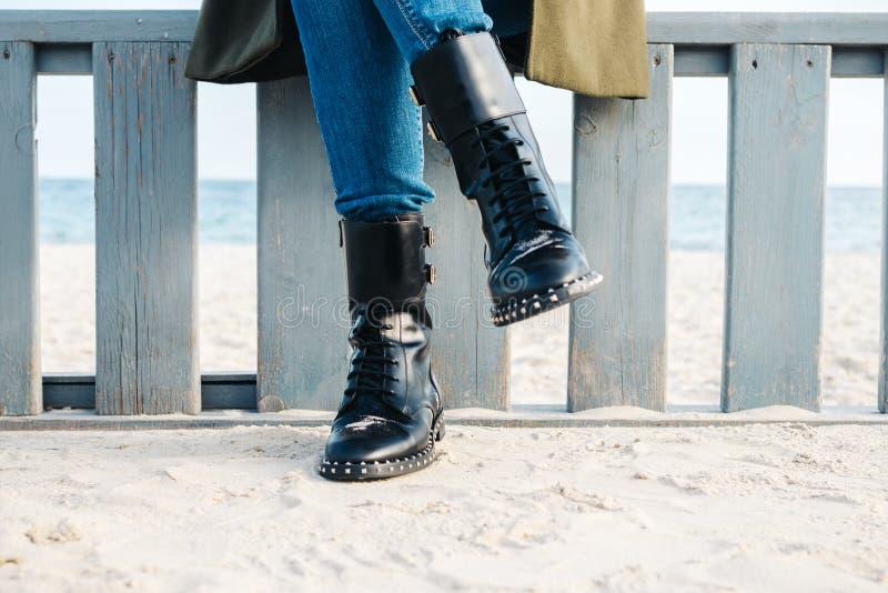 Nahaufnahme von weiblichen Beinen in den schwarzen Stiefeln und in den Jeans stockfoto