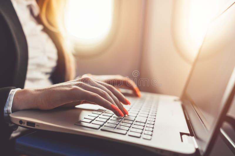 Nahaufnahme von weiblichen Händen unter Verwendung des Laptops Frauenfunktion beim auf Geschäftsreise mit dem Flugzeug gehen lizenzfreie stockfotografie