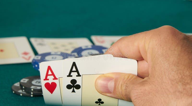 Nahaufnahme von zwei Assen gehalten in einer Hand auf der gr?nen Spielmatte auf der rechten Seite des Bildes, um Raum f?r das Red stockfoto