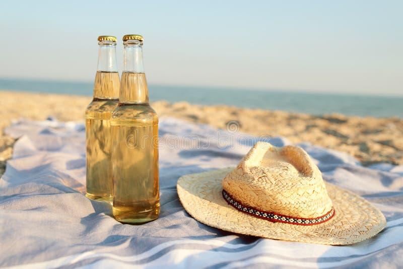 Nahaufnahme von zwei Bierglasflaschen auf sandigem tropischem Badetuch nahe Strohhut Blaue Ozeanlagune auf Hintergrund lizenzfreie stockfotografie