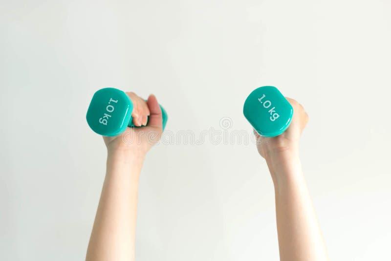 Nahaufnahme von zwei Händen, die Dummköpfe oben auf weißem Hintergrund anheben stockfoto