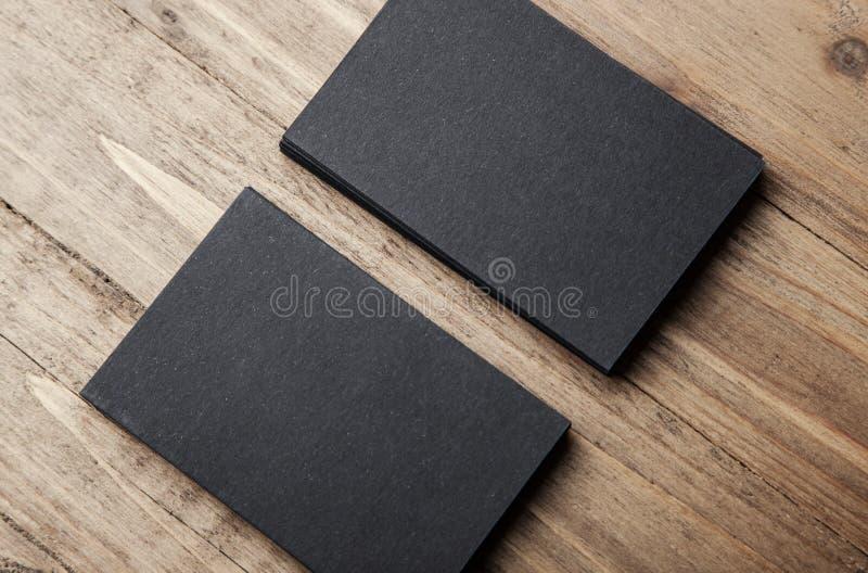 Nahaufnahme von zwei Stapel leeren schwarzen Visitenkarten auf hölzernem Hintergrund lizenzfreie stockbilder
