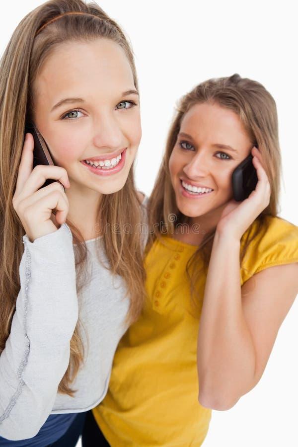 Nahaufnahme von zwei Studenten, die am Telefon lächeln stockfoto