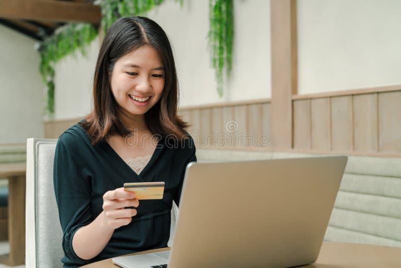 Nahaufnahme, welche die asiatische Schönheit, die ein schwarzes Hemd sitzt im Haus trägt, eine Kreditkarte in der Hand haben, kau stockfotos