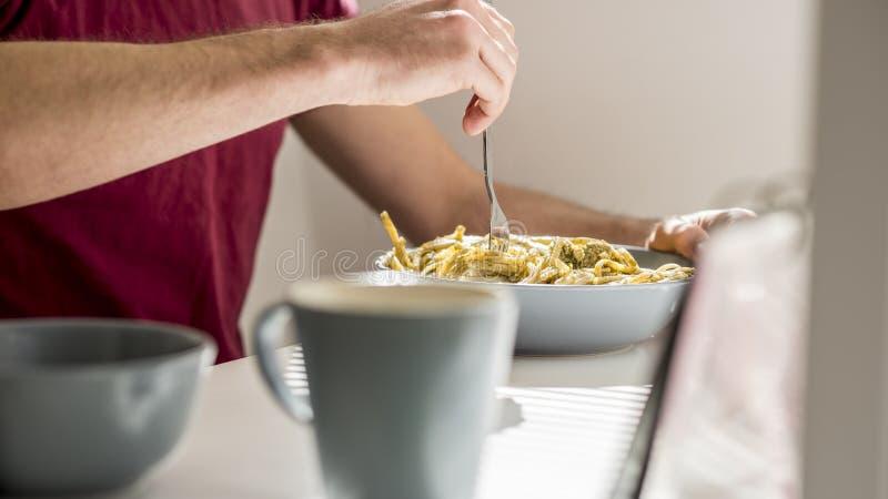 Nahaufnahme wirbelnden Spaghettis des Mannes mit Pestosoße mit einer Gabel stockfoto
