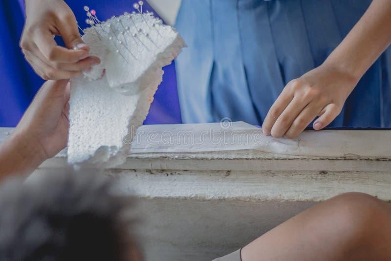 Nahaufnahme zu den Studentenhänden verzieren die Vorhänge decorate stockfotos