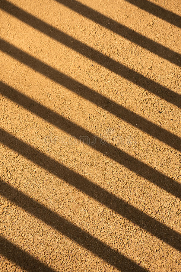 Nahaufnahmeabschnitt des Zauns mit diagonalen Schatten lizenzfreie stockbilder