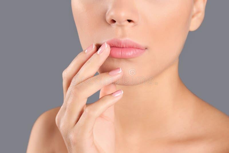 Nahaufnahmeansicht der schönen jungen Frau auf grauem Hintergrund Umreißende Lippen, Hautpflege stockbilder