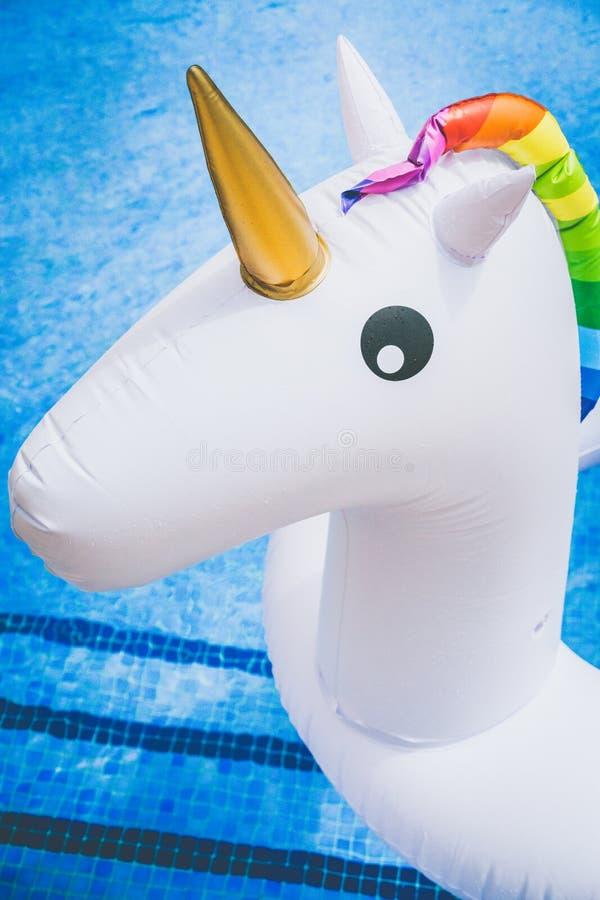 Nahaufnahmeansicht des aufblasbaren bunten weißen Einhorns am Swimmingpool Spaßzeit im Sommer am Swimmingpool Konzept lizenzfreie stockfotos
