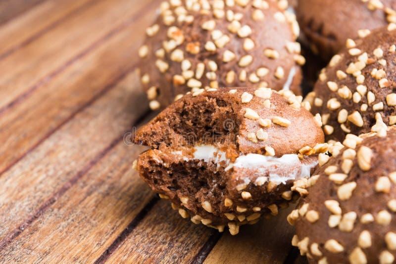 Nahaufnahmeansicht des Beißens des Schokoladenplätzchens über braunem hölzernem Vorsprung lizenzfreie stockfotografie
