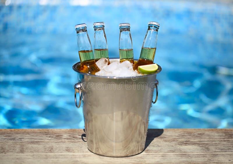 Nahaufnahmeansicht des Eimers mit Eiswürfeln, Bierflaschen und Kalkscheiben stockbild