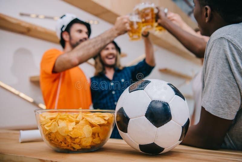 Nahaufnahmeansicht des Fußballs und der Schüssel mit Chips mit der Gruppe Fußballfanen hinten feiernd und durch Biergläser klirre lizenzfreie stockfotografie