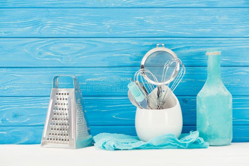 Nahaufnahmeansicht des Lappens, Flasche, Gebäckbürste, Reibe, wischt und Sieb vor Blau stockfotografie
