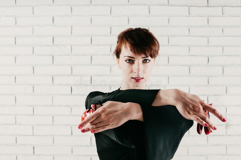 Nahaufnahmeansicht einer hübschen Frau im schwarzen Kleid, tanzend mit Rot stockfotografie