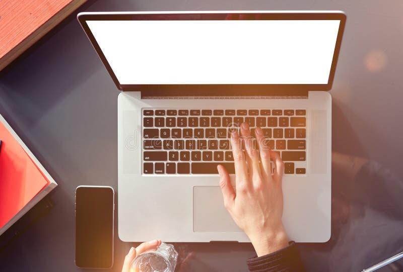Nahaufnahmeansicht-Frauenhände über von der Anwendung des Laptops und des mobilen Smartphone Dachbodeninnentageslicht, graue Tabe lizenzfreie stockfotografie