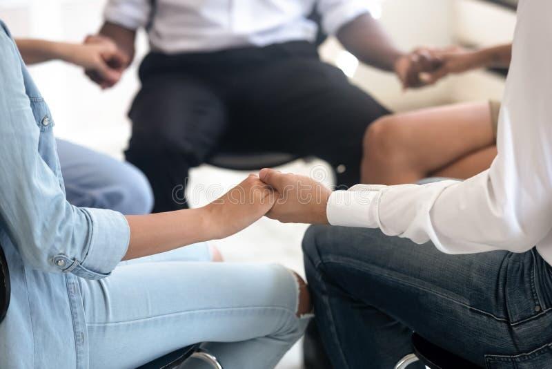 Nahaufnahmeansichtleute, die auf Stühlen im Kreishändchenhalten sitzen stockbild
