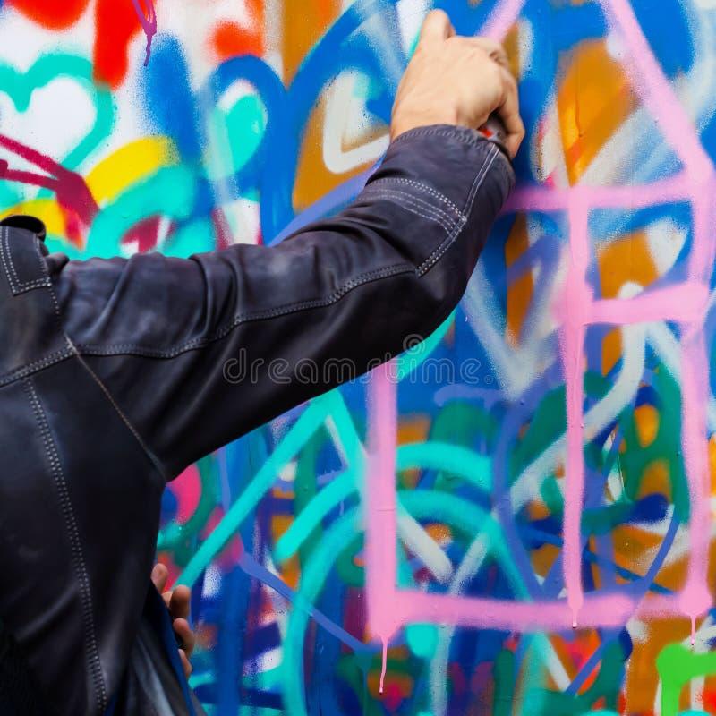 Nahaufnahmearm des jungen Kerls bunte Graffiti auf der Wand, modernes Design des Konzeptes zeichnend lizenzfreies stockfoto