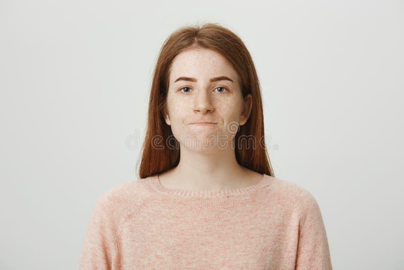 Nahaufnahmeatelieraufnahme der gestörten oder gestörten Rothaarigefrau mit ausgedehntem unglücklichem Lächeln, stehend über graue stockbilder