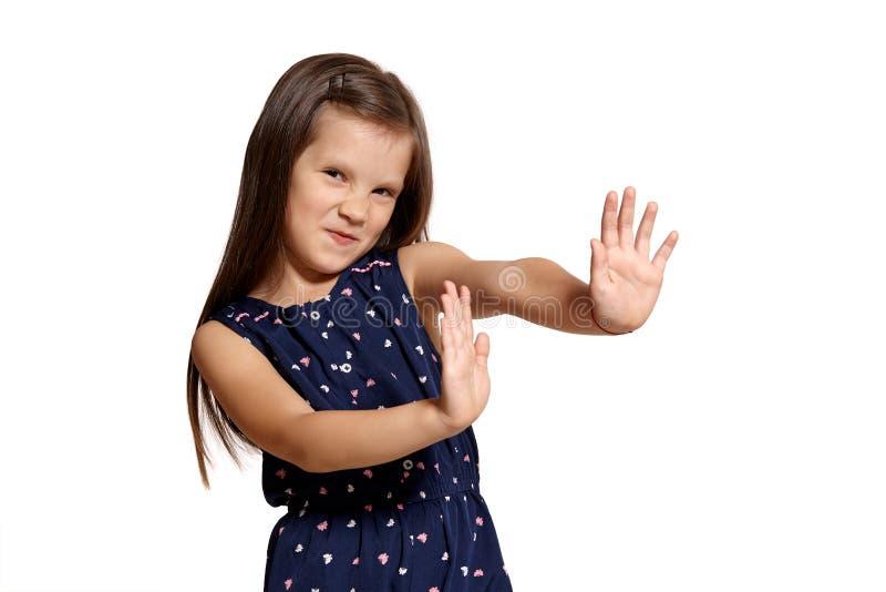 Nahaufnahmeatelieraufnahme der schönen brunette Aufstellung des kleinen Mädchens lokalisiert auf weißem Studiohintergrund stockbild