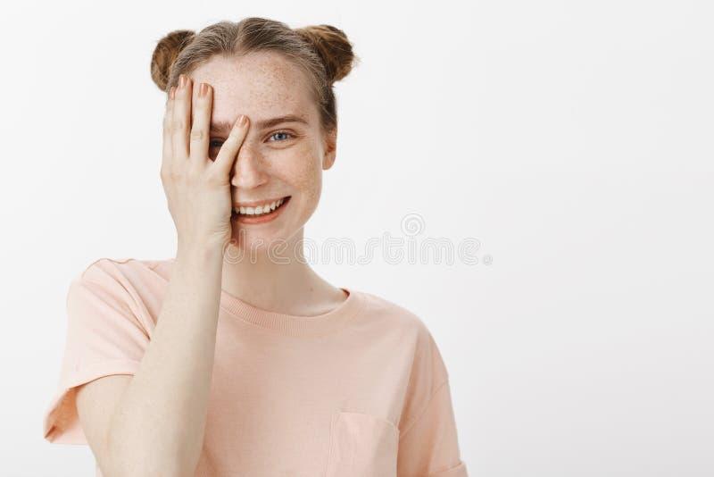 Nahaufnahmeatelieraufnahme der schönen natürlichen europäischen Frau mit netter Sommersprosse- und Brötchenfrisur, halb bedeckend stockbilder