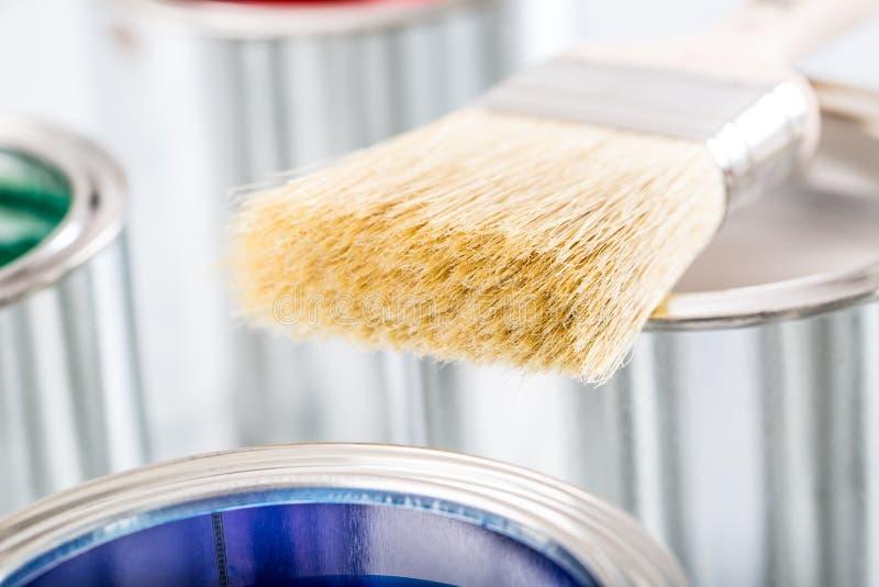 Nahaufnahmebürste, die auf mehrfarbigen Farbendosen liegt lizenzfreie stockbilder