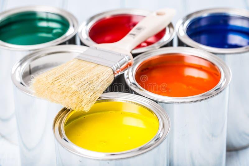 Nahaufnahmebürste, die auf mehrfarbigen Farbendosen liegt lizenzfreie stockfotos