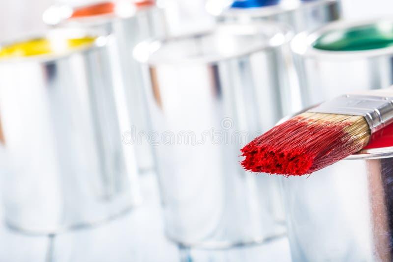 Nahaufnahmebürste mit der roten Farbe, die auf Farbendose liegt stockfotografie