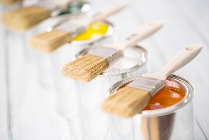 Nahaufnahmebürsten, die auf mehrfarbigen Farbendosen liegen lizenzfreie stockbilder