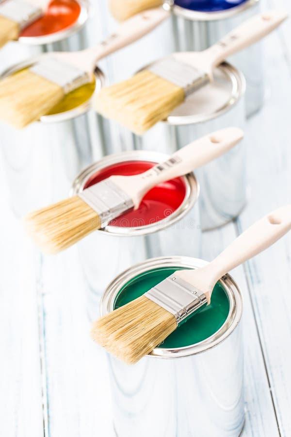 Nahaufnahmebürsten, die auf mehrfarbigen Farbendosen liegen lizenzfreies stockfoto
