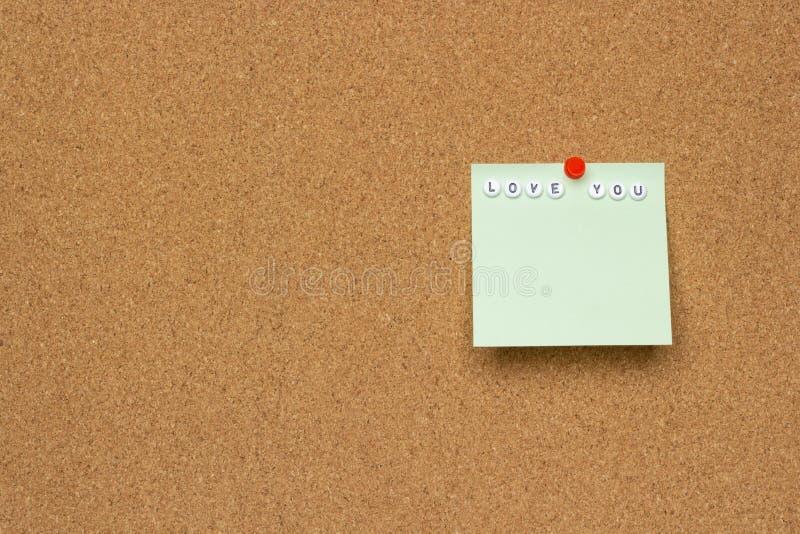 Nahaufnahmebeschaffenheit eines braunen Korkenbrettblattes mit einem Blatt Papier und Wortliebe Sie lizenzfreie stockfotografie