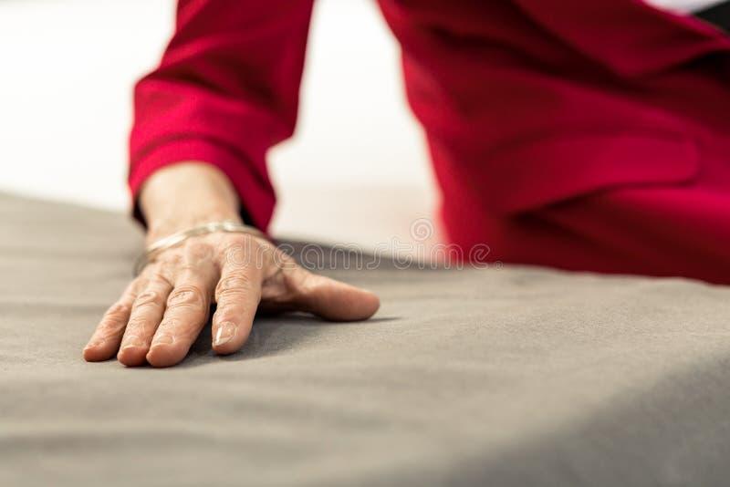 Nahaufnahmebild alternder Damenhand, die auf Bettlaken liegt stockbilder