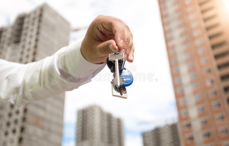 Nahaufnahmebild der Geschäftsmannhand Schlüssel von der neuen Wohnung halten Konzept der Immobilieninvestition stockfotos