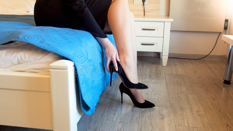 Nahaufnahmebild der jungen Frau sitzend auf Bett im Hotel und Schuhe der hohen Absätze entfernend lizenzfreie stockfotos