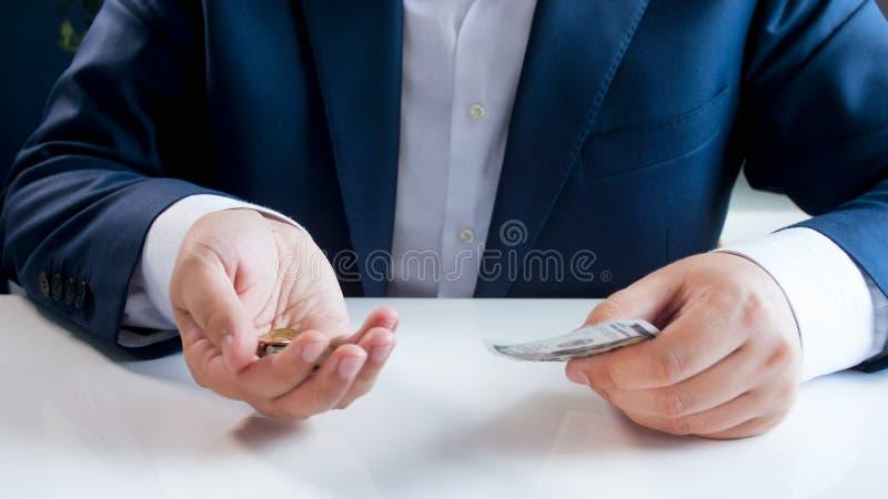 Nahaufnahmebild des Geschäftsmannes Münzen in einer Hand und Kreditkarte in anderer halten lizenzfreie stockfotografie
