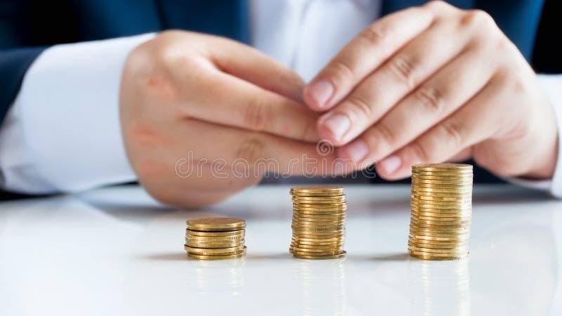 Nahaufnahmebild des Geschäftsmannes sitzend hinter Schreibtisch mit drei Stapeln der goldenen Münzen stockbilder