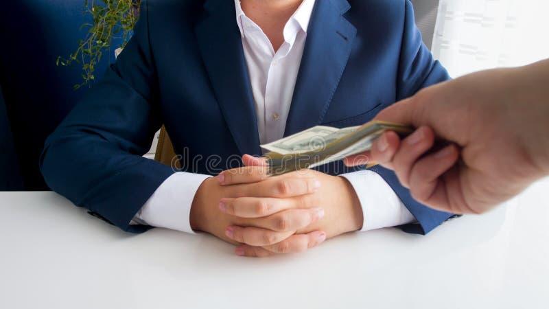 Nahaufnahmebild des Handholdingstapels Geldes ausdehnend in Richtung zum Geschäftsmann, der im Büro sitzt lizenzfreie stockfotografie