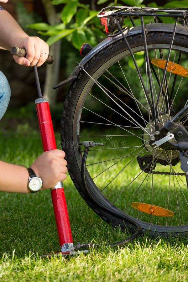 Nahaufnahmebild des jungen Mannes flachen Fahrradreifen pumpend lizenzfreie stockfotografie