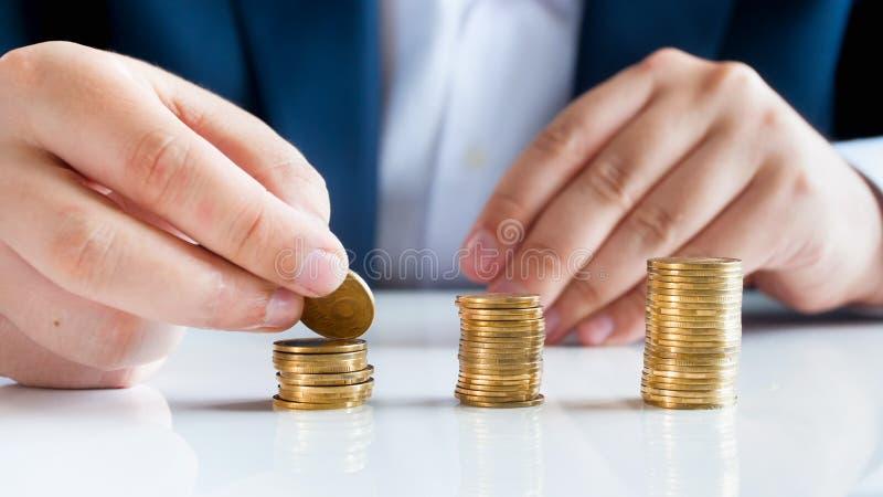 Nahaufnahmebild des männlichen Bankers goldene Münzen in Hochstapel auf Schreibtisch einsetzend stockbilder