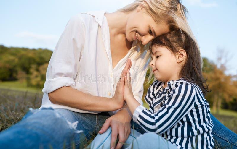 Nahaufnahmebild des netten kleinen Mädchens, das mit ihrer lächelnden glücklichen Mutter spielt Liebende Schönheit und ihre Tocht stockfotos