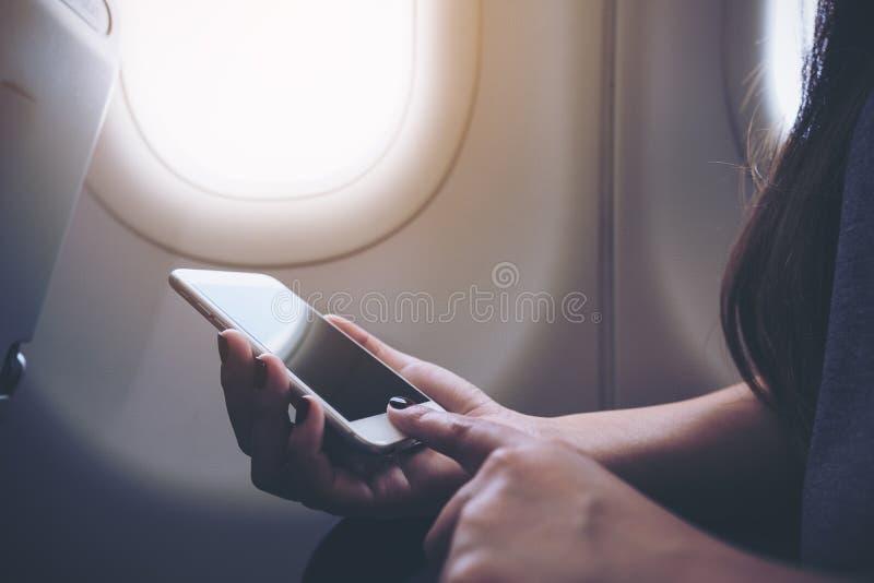 Nahaufnahmebild einer Frau, die am weißen intelligenten Telefon nahe bei einem Flugzeugfenster mit Wolken und Himmel hält und sic stockfoto